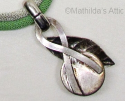 reverse side of green and white enamel flower pendant