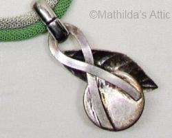 reverse side of green and white enamel flower pendant