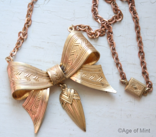 1930s brass bow on coppertone chain detail