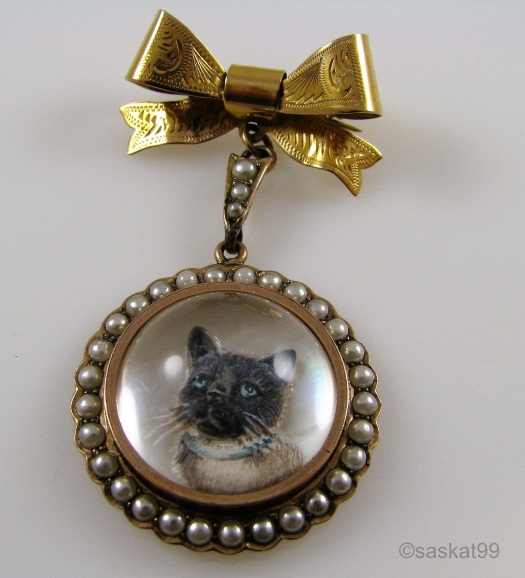 """Cat portrait set with pearls, below a gold bow brooch hallmarked by Ward Bros in Birmingham (WB), 1895 (V) and gold content (9k). About 2 1/4"""" diameter."""