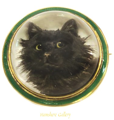 Black cat brooch, set in 18k gold and trimmed in green enamel. European, early 1900s.