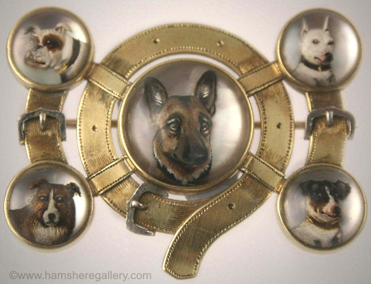 Brooch depicting five dog breeds: Boxer, Bull Terrier, Jack Russell, Collie and German Shepherd. Gold dog-collar mounting has platinum accents.