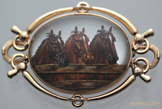 14k gold brooch in an equestrian design, with crystal showing three horses.