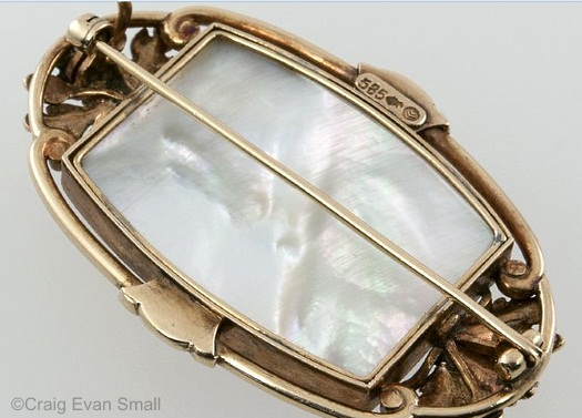 Gold brooch with oak leaves and acorns framing two horse heads; mother of pearl reverse.